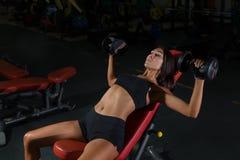 Allenamento di forma fisica in palestra, donna esile con le teste di legno Fotografia Stock