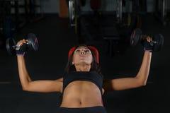 Allenamento di forma fisica in palestra, donna esile con le teste di legno Immagine Stock