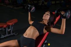Allenamento di forma fisica in palestra, donna esile con le teste di legno Immagini Stock
