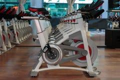 Allenamento di forma fisica in palestra: Gruppo di bici di filatura moderne nella linea Immagini Stock