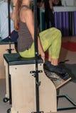 Allenamento di forma fisica in palestra: Ragazza che fa esercizio sulla sedia di legno Immagine Stock Libera da Diritti