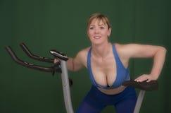 Allenamento di forma fisica prima di per mezzo di una bici di esercizio Fotografia Stock Libera da Diritti