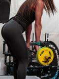Allenamento di forma fisica: Ragazza graziosa che utilizza bilanciere nella palestra Fotografie Stock