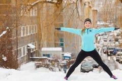 Allenamento di inverno Abiti sportivi d'uso della ragazza, allunganti gli esercizi Fotografia Stock