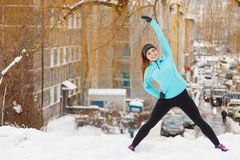 Allenamento di inverno Abiti sportivi d'uso della ragazza, allunganti gli esercizi Immagine Stock