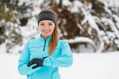 Allenamento di inverno Abiti sportivi d'uso della ragazza che controllano tempo Fotografia Stock Libera da Diritti