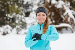 Allenamento di inverno Abiti sportivi d'uso della ragazza che controllano tempo Immagini Stock