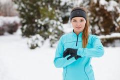 Allenamento di inverno Abiti sportivi d'uso della ragazza che controllano tempo Fotografie Stock Libere da Diritti
