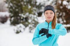 Allenamento di inverno Abiti sportivi d'uso della ragazza, esaminanti orologio Immagini Stock