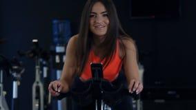 Allenamento di modello di giovane misura sexy in palestra sulla bici di esercizio