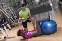 Allenamento di Pilates con l'istruttore personale alla palestra Fotografie Stock