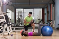 Allenamento di Pilates con l'istruttore personale alla palestra Fotografia Stock