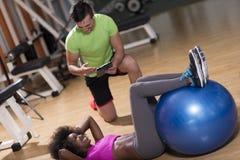 Allenamento di Pilates con l'istruttore personale alla palestra Fotografia Stock Libera da Diritti