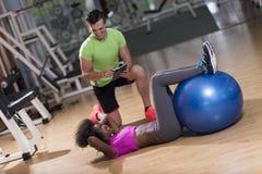 Allenamento di Pilates con l'istruttore personale alla palestra Immagini Stock