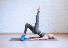 Allenamento di Pilates Donna nel vestito grigio di sport che fa esercizio su per la matematica con il rullo di forma fisica, fond immagini stock