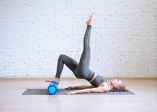 Allenamento di Pilates Donna nel vestito grigio di sport che fa esercizio su per la matematica con il rullo di forma fisica, fond fotografie stock