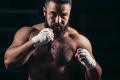 Allenamento di pugilato dell'uomo sull'anello Pugile maschio caucasico in guanti neri Immagini Stock