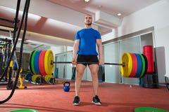 Allenamento di sollevamento pesante dell'uomo della barra della palestra di forma fisica di Crossfit Immagini Stock