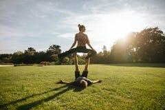 Allenamento di yoga di Acro su erba Immagine Stock