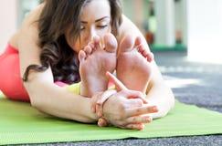 Allenamento di yoga Giovane ragazza graziosa che allunga le gambe Fotografie Stock