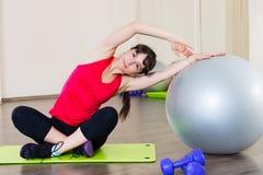 Allenamento di forma fisica della giovane donna in palestra con fitball Fotografie Stock Libere da Diritti