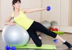 Allenamento di forma fisica della giovane donna in palestra con fitball Fotografia Stock