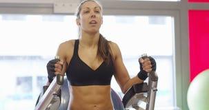 Allenamento messo a fuoco della donna di forma fisica il suo ABS nella palestra di forma fisica archivi video