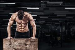Allenamento muscolare bello dell'uomo alla palestra del crossfit Fotografia Stock