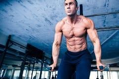 Allenamento muscolare bello dell'uomo sulle barre Fotografia Stock Libera da Diritti