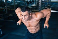 Allenamento muscolare bello dell'uomo sulle barre Fotografie Stock Libere da Diritti