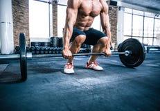 Allenamento muscolare dell'uomo con il bilanciere Fotografia Stock