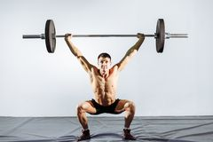 Allenamento muscolare dell'uomo con il bilanciere alla palestra Immagine Stock