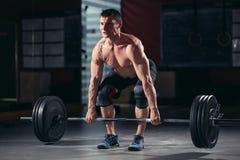 Allenamento muscolare dell'uomo con il bilanciere alla palestra Immagini Stock