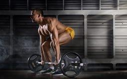 Allenamento muscolare dell'uomo con il bilanciere alla palestra Fotografie Stock