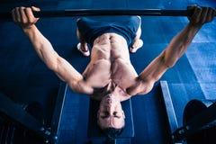 Allenamento muscolare dell'uomo con il bilanciere sul banco Fotografia Stock