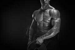 Allenamento muscolare dell'uomo con il piatto del bilanciere Immagine Stock
