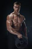 Allenamento muscolare dell'uomo con il piatto del bilanciere Fotografia Stock Libera da Diritti