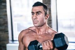 Allenamento muscolare dell'uomo con la testa di legno Immagini Stock