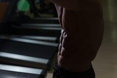 Allenamento muscolare dell'uomo con le teste di legno nella stanza scura Fotografia Stock Libera da Diritti