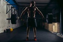 Allenamento muscolare dell'uomo in palestra che fa gli esercizi con il bilanciere Fotografie Stock