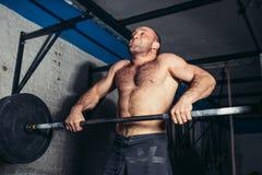 Allenamento muscolare dell'uomo in palestra che fa gli esercizi con il bilanciere Immagine Stock