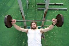 Allenamento muscolare dell'uomo in palestra che fa gli esercizi con il bilanciere Immagini Stock Libere da Diritti