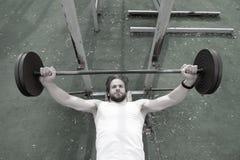 Allenamento muscolare dell'uomo in palestra che fa gli esercizi con il bilanciere Immagini Stock