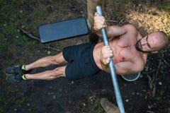 Allenamento muscolare dell'uomo sulle barre in palestra all'aperto Fotografia Stock