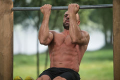 Allenamento muscolare dell'uomo sulle barre in palestra all'aperto Fotografie Stock Libere da Diritti