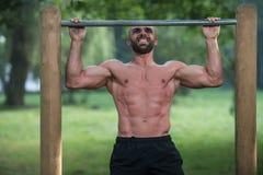 Allenamento muscolare dell'uomo sulle barre in palestra all'aperto Immagine Stock