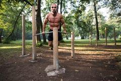 Allenamento muscolare dell'uomo sulle barre in palestra all'aperto Fotografie Stock