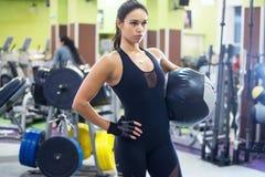 Allenamento muscolare della donna di misura in palestra Forte femmina Immagini Stock