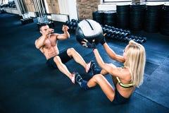 Allenamento muscolare della donna e dell'uomo con fitball Immagini Stock