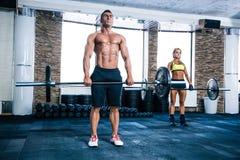 Allenamento muscolare della donna e dell'uomo con il bilanciere Fotografie Stock